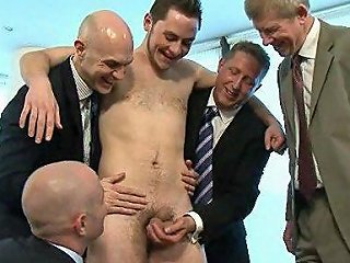 A Group Of Bosses In Suits Are Abusing This Young Fellow And Jerk Off His Cock In Office