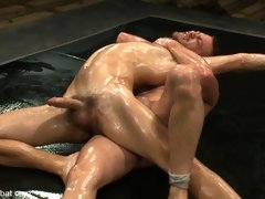 Two muscle gods wrestle naked in oil.